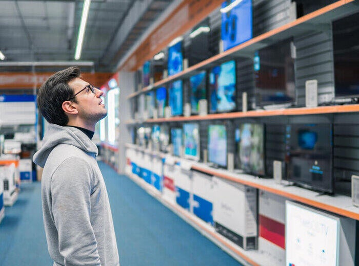 In a large store, a man looks interestedly at shelves with various sizes of televisions.