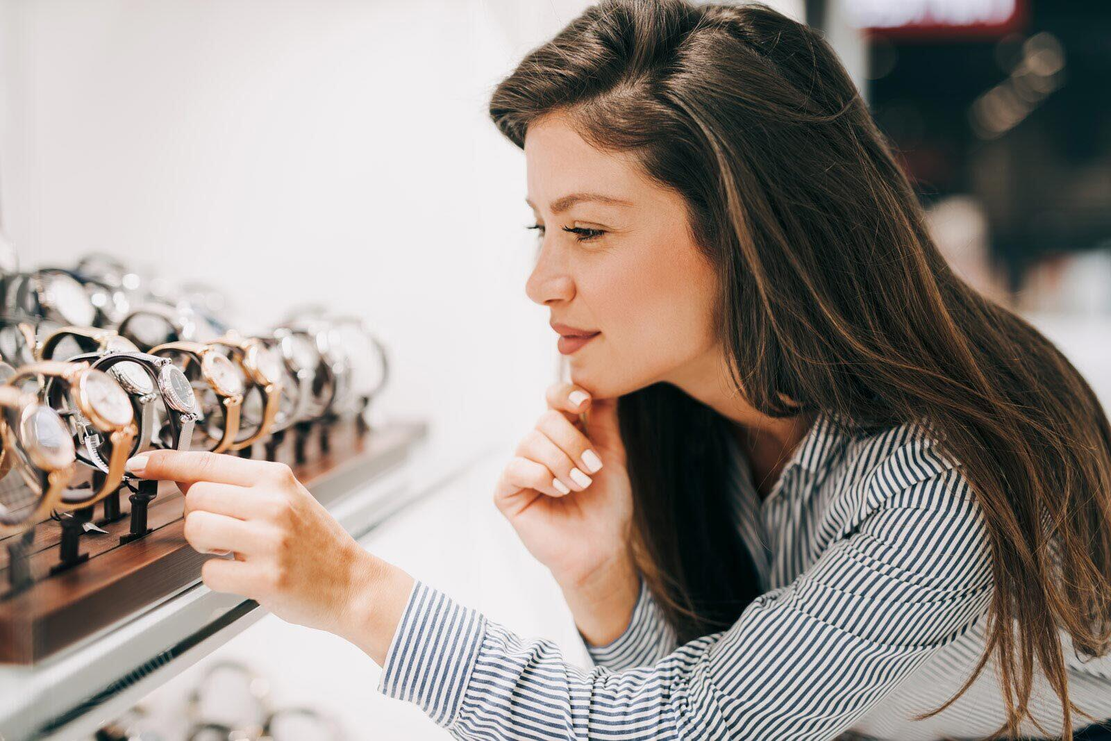 A woman in a store looking at a selection of jewelry.