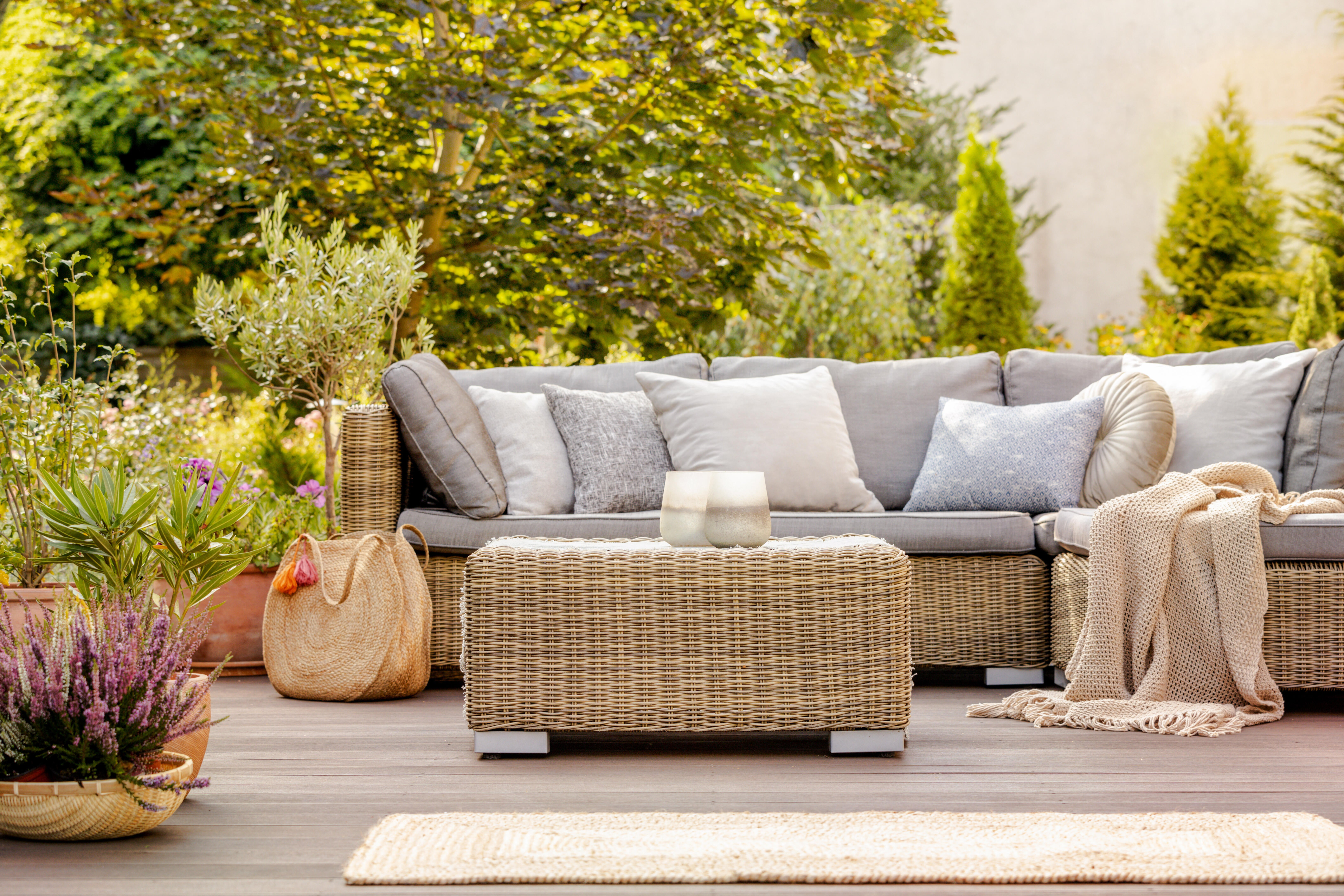 An outdoor patio furniture set is surrounded by plants and trees.