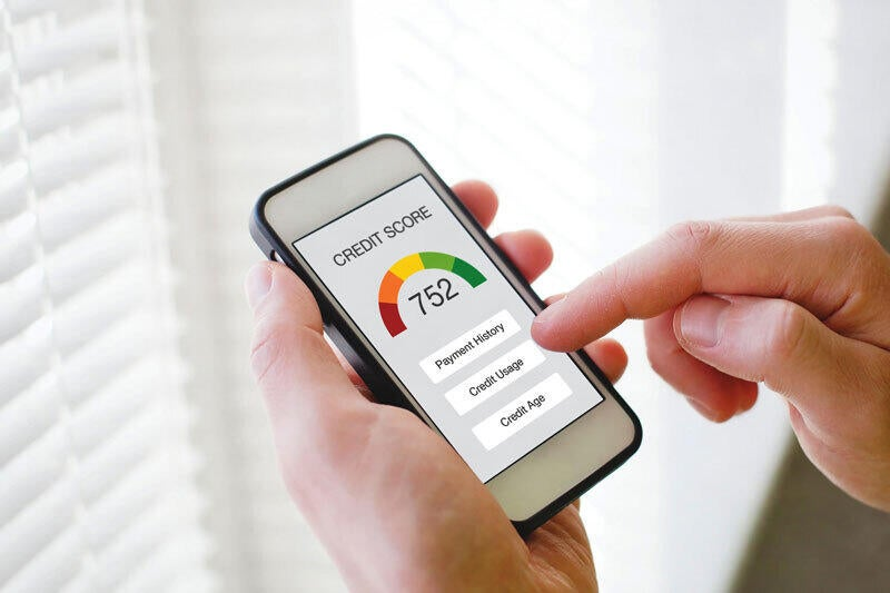 A person is holding their smartphone and looking at their credit score.