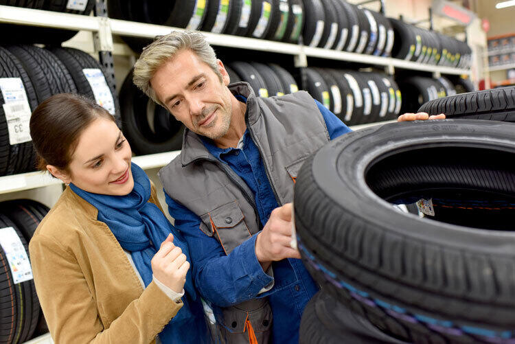 A woman and a store representative are looking at tires.
