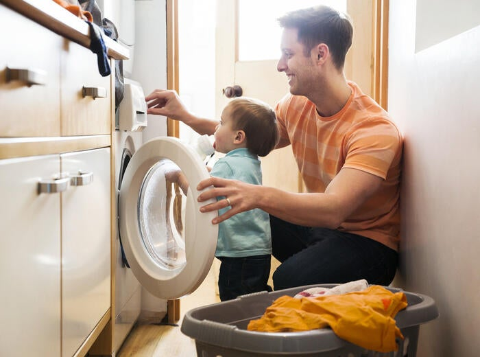 A father and son are loading a washing machine.
