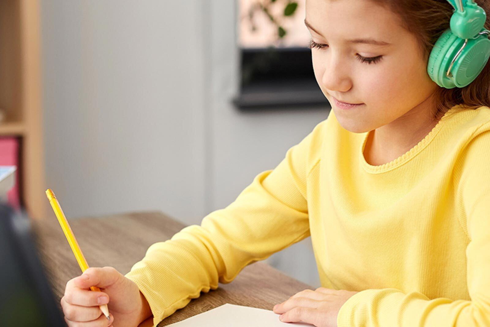 A child is studying at a desk with her headphones on.