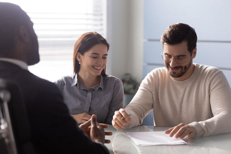 A couple is sitting at a table looking at papers and talking to a store representative.