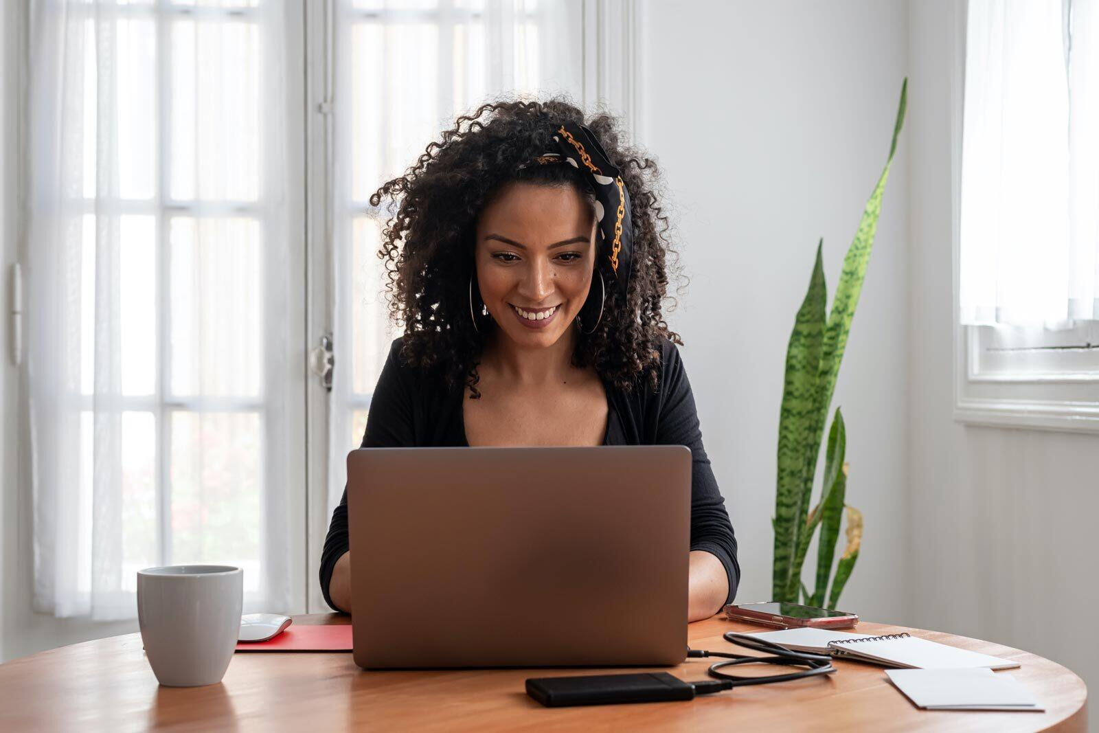 A woman with a smile is working on a laptop.